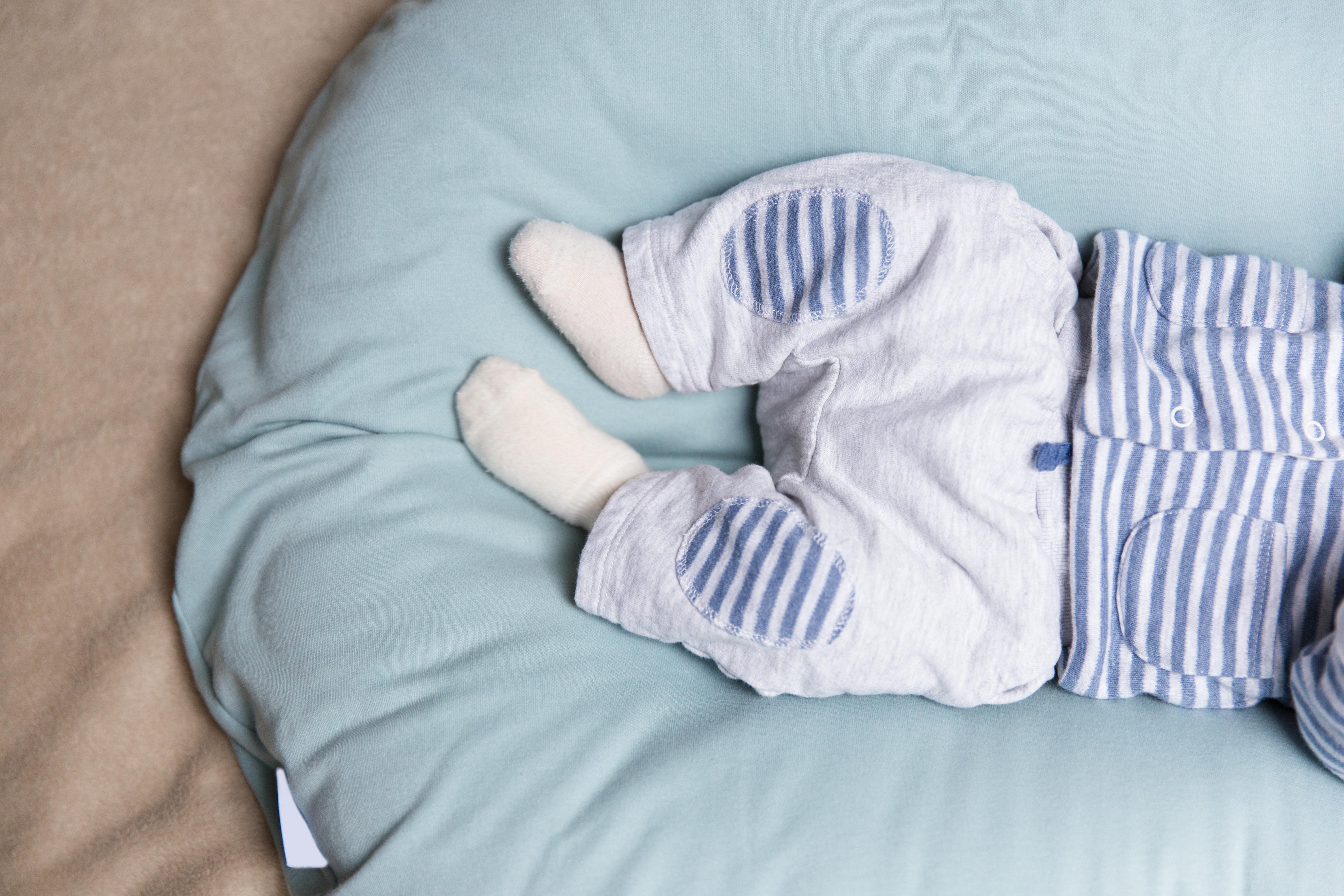 Medio cuerpo de un bebe acostado sobre un cojin azul