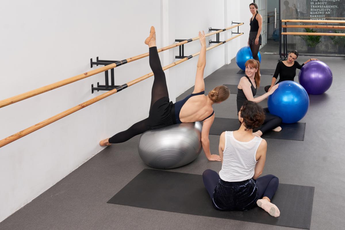 Profesora de ballet barre mostrando un ejercicio sobre la pelota de pilates