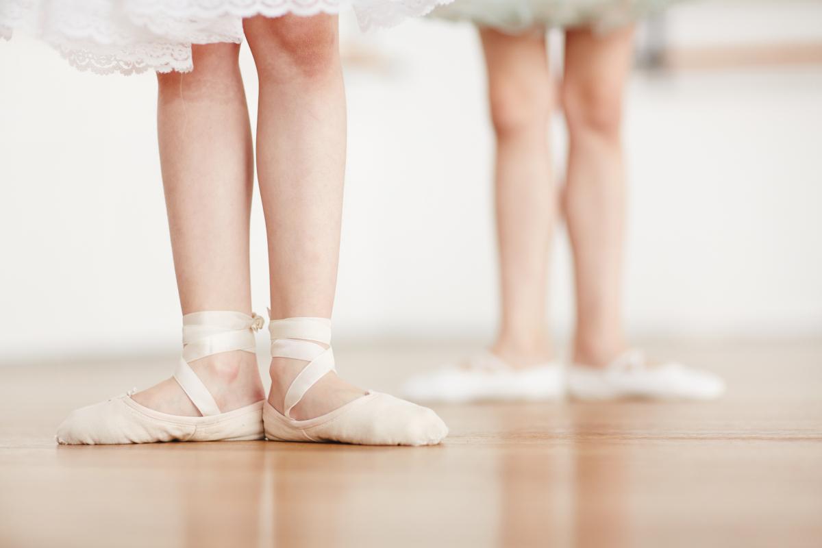 Piernas de unas pequeñas bailarinas en el suelo con zapatillas de ballet