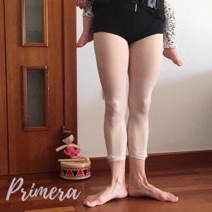 Medio cuerpo donde se ve las piernas de una mujer en primera posición de ballet. Se ven las piernas de un bebé por detrás.