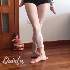 medio cuerpo de una bailarina con un bebe en la espalda mostrando la quinta posición de piernas en ballet