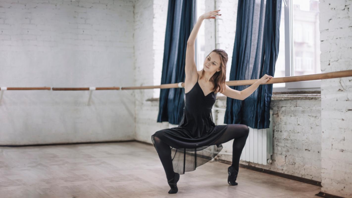 Bailarina en barra vestida de negro haciendo un grand plié en segunda posición
