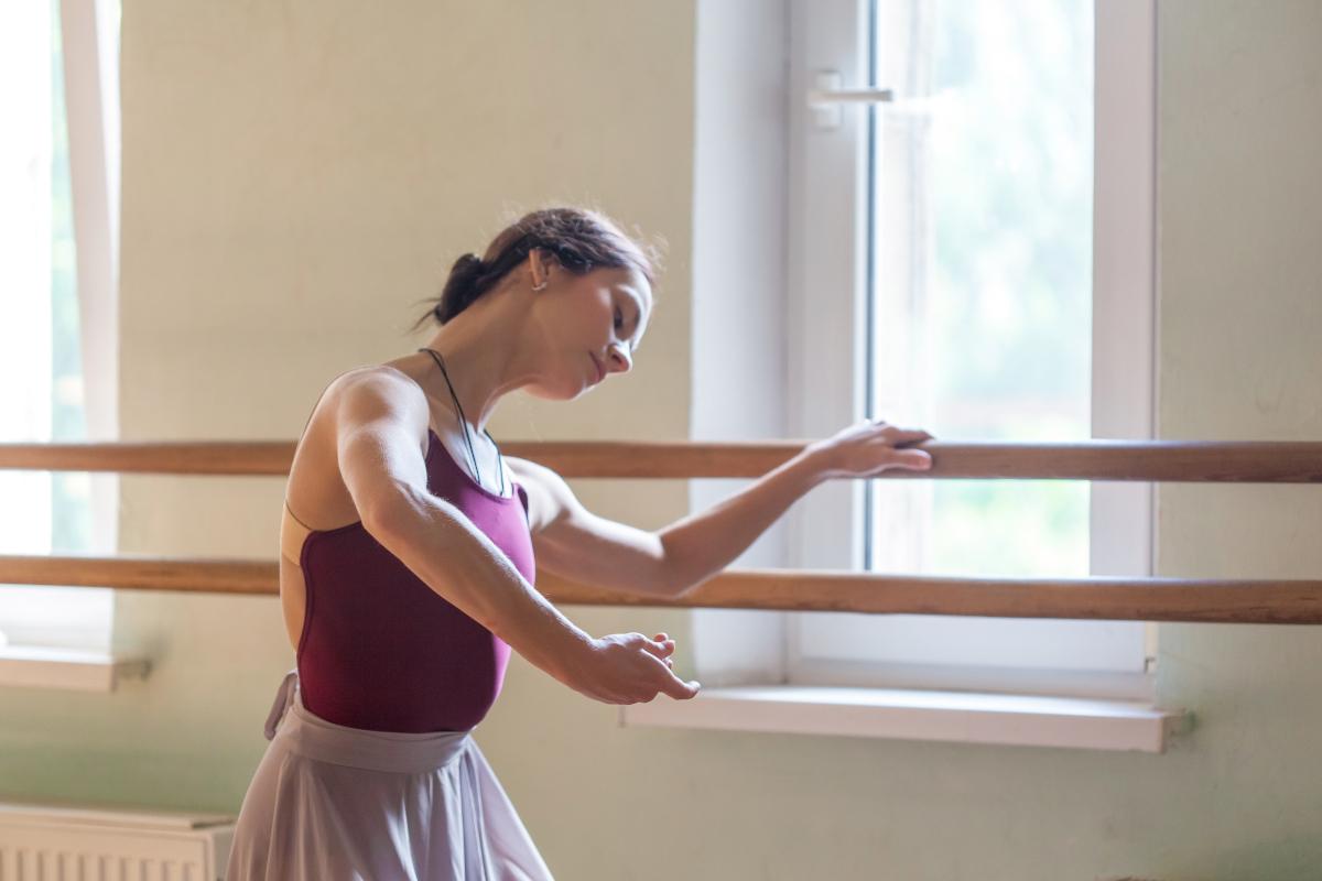 una chica vestida de morado haciendo ballet sobre la barra