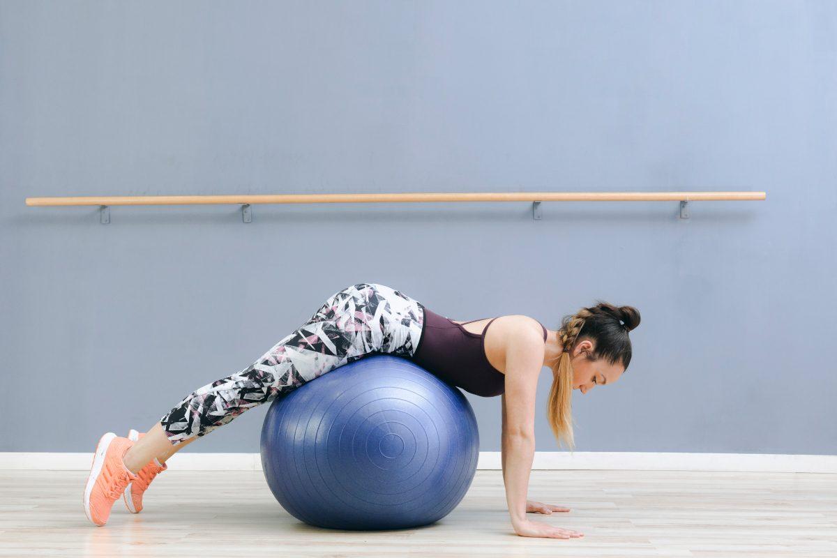 Chica tumbada sobre fitball azul y barra de ballet detrás