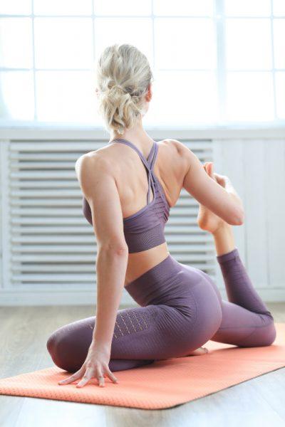 una chica haciendo yoga en casa de espaldas vestida de morado y con la esterilla naranja