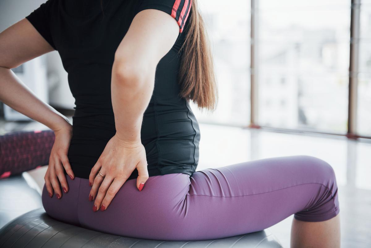 mujer embarazada sentada sobre fitball de espaldas