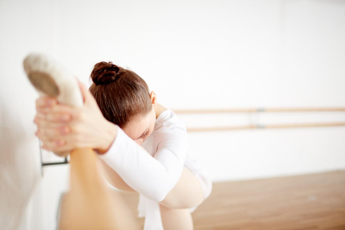 Bailarina subiendo la pierna en el la barra estirando
