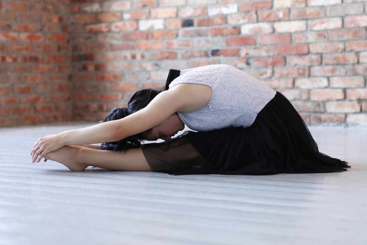 Una mujer estirando sobre el suelo en un estudio de ballet