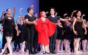 Alicia Alonso vestida de rojo saludando al publico junto al elenco de bailarines