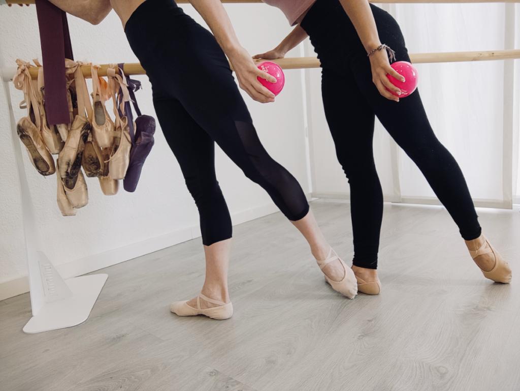 piernas de dos instructoras de barre sosteniendo una pelota rosa en la mano