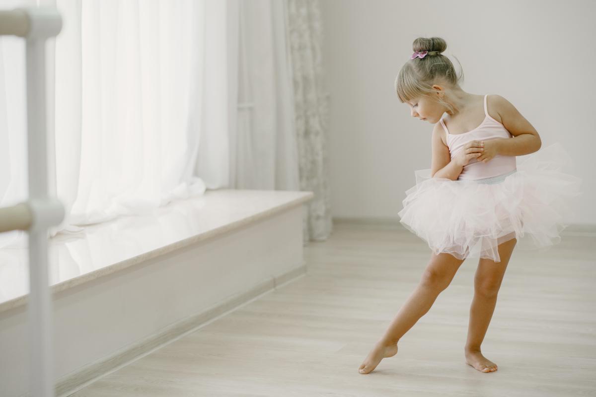 Una niña de 6 años vestida de blanco con tutu y maiot haciendo ballet descalza