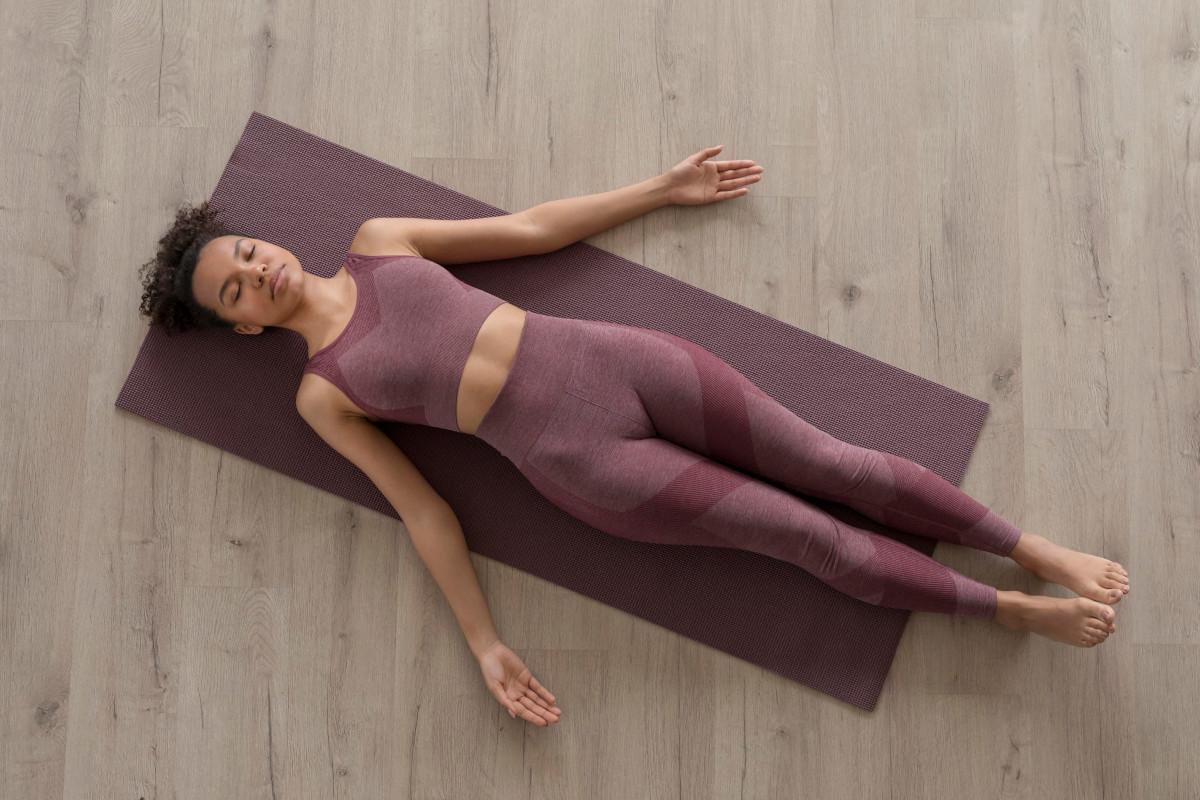 Mujer vestida de morado tumbada encima de una esterilla relajándose después de una clase de floor barre